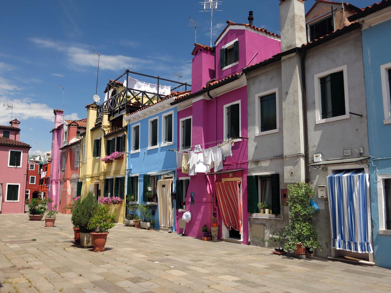 Colorful houses in campo (square) with clothes drying in Burano